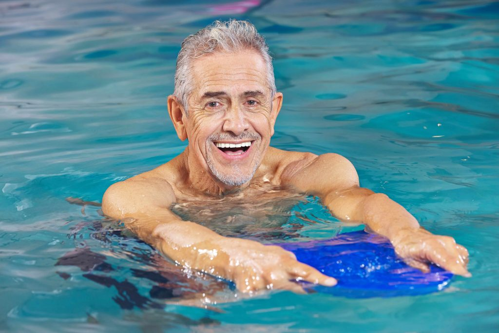 a close-up of a smiling older man in a swimming pool, holding a kickboard