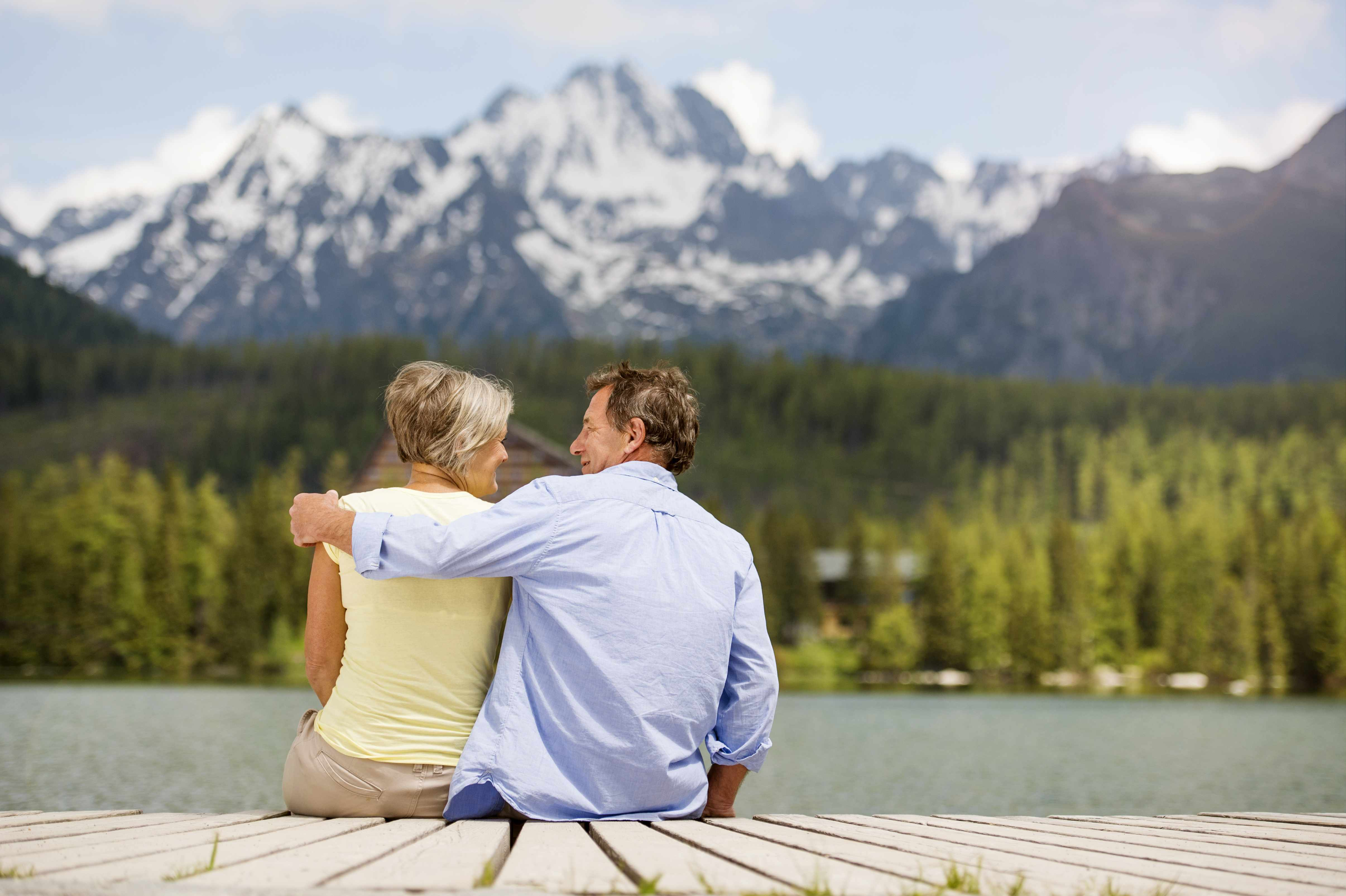 a middle-aged couple sitting on a boat dock near water, a lake, looking at the beautiful forest and mountains