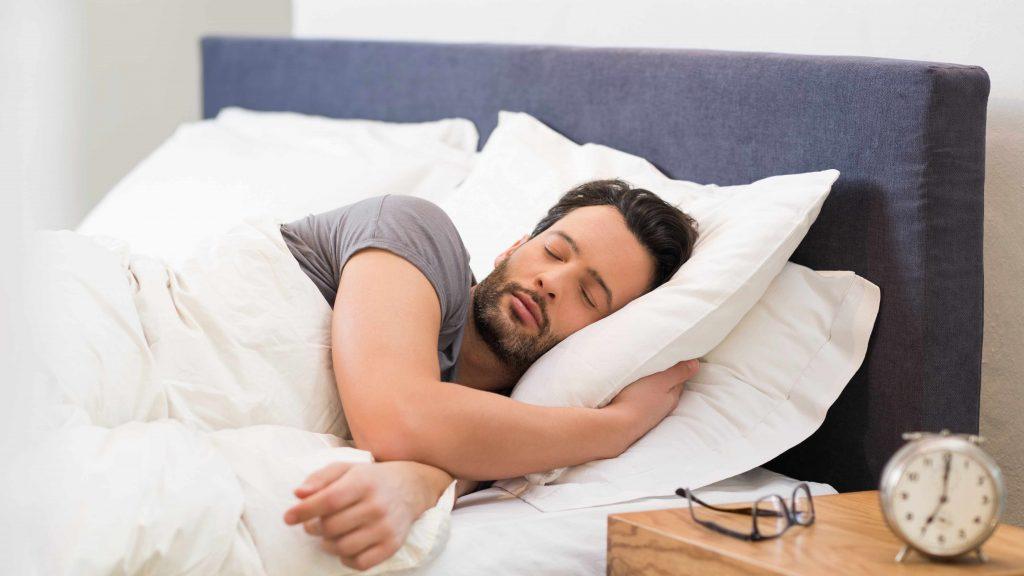 Un hombre duerme serenamente y en paz con un despertador delante