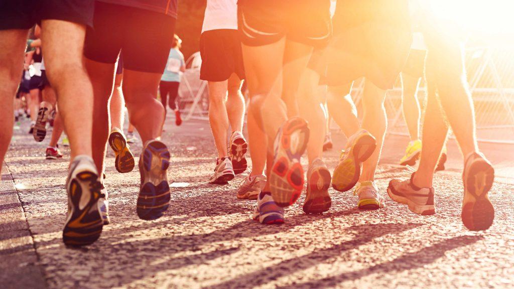 vista desde atrás de los pies y de las piernas de varios corredores, con la luz del sol filtrándose en medio