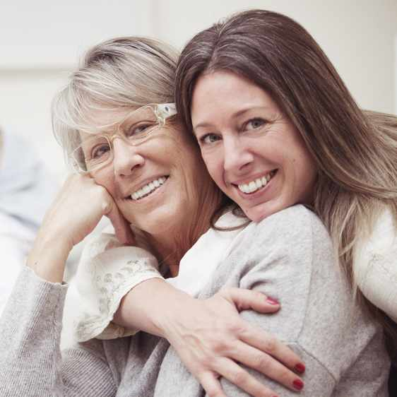 a smiling woman hugging her smiling mother