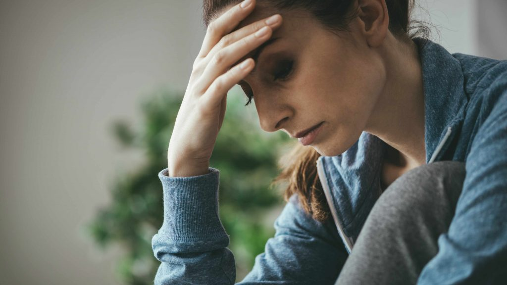 Una mujer se sostiene la cabeza mientras se muestra triste, deprimida y con pensamientos negativos