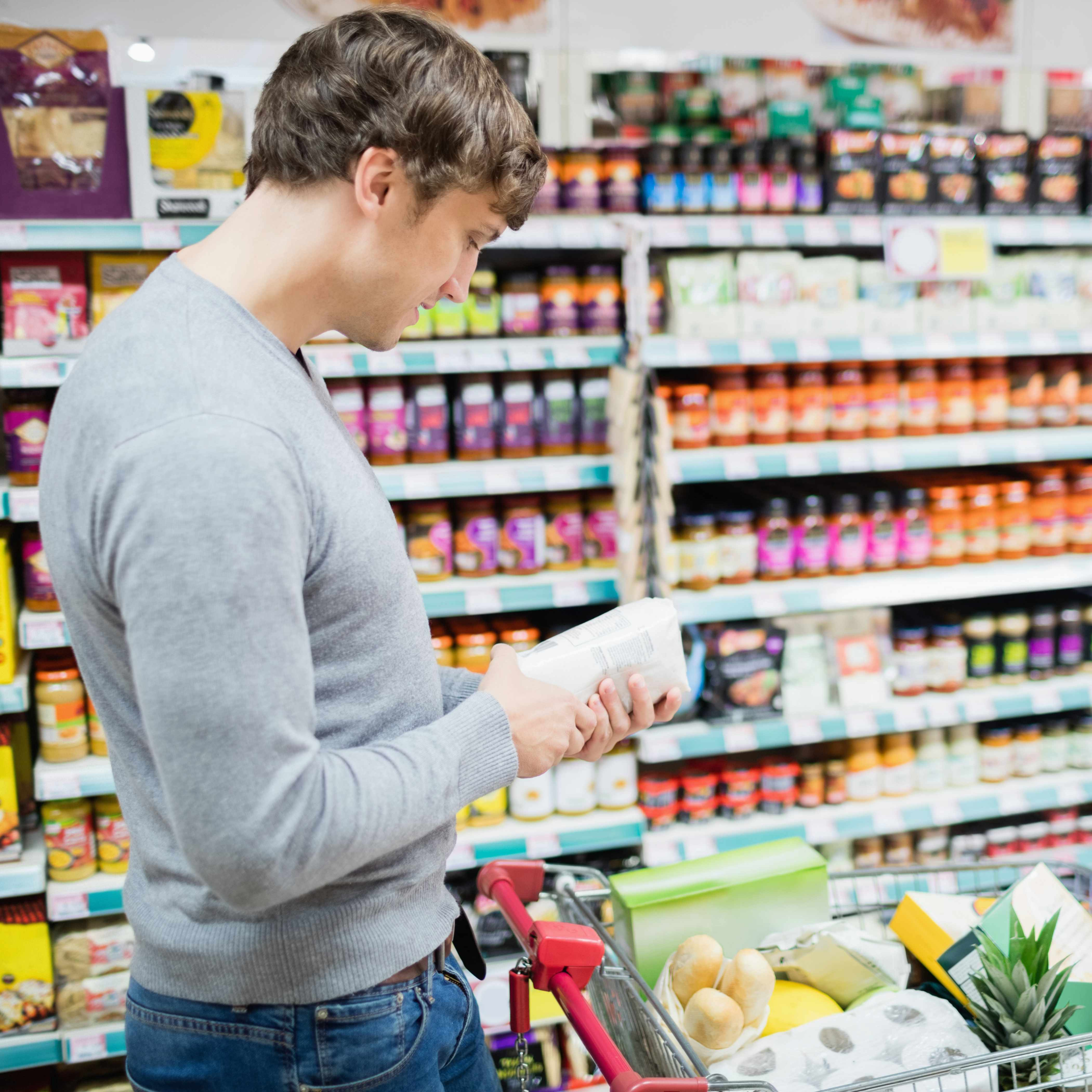 a young man shopping in a grocery store holding a can and reading the nutrition food label