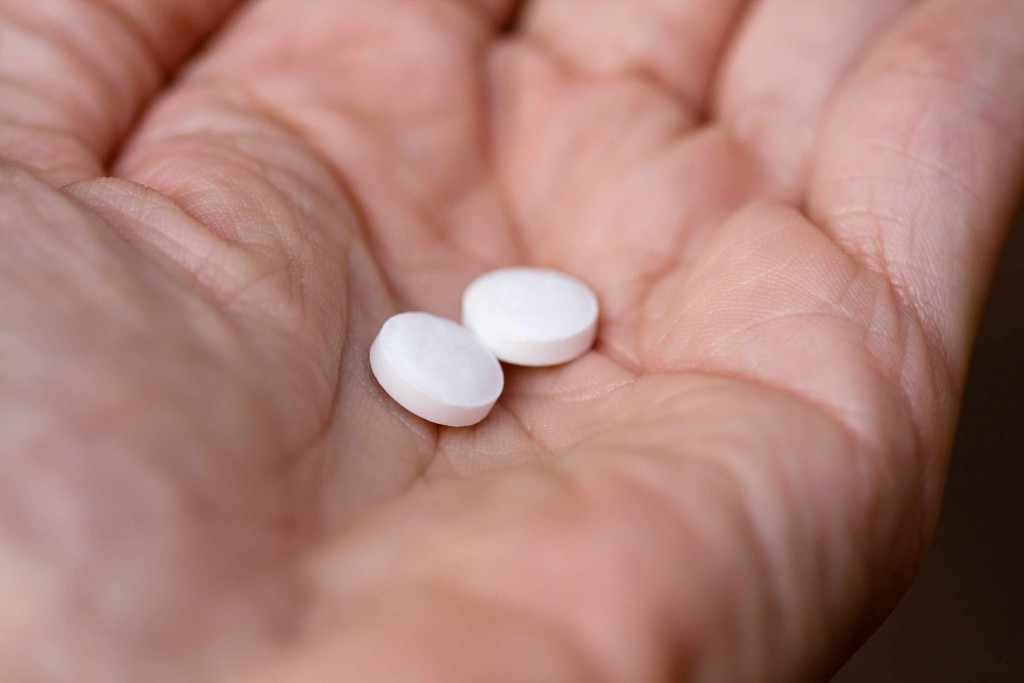hand holding two aspirin tablets pills