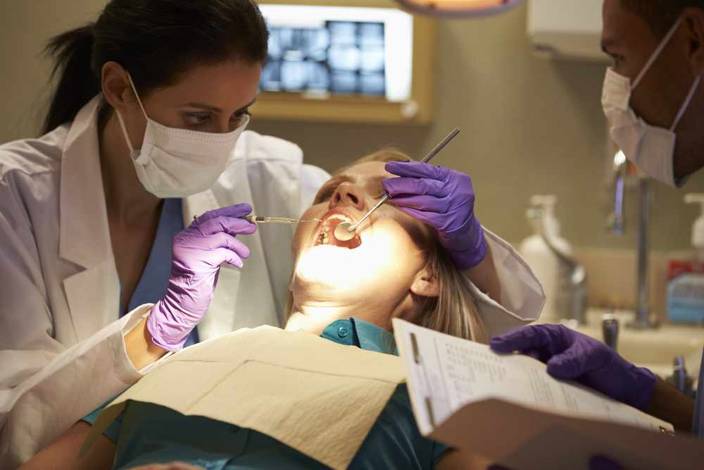 Dentists performing dental exam on female patient