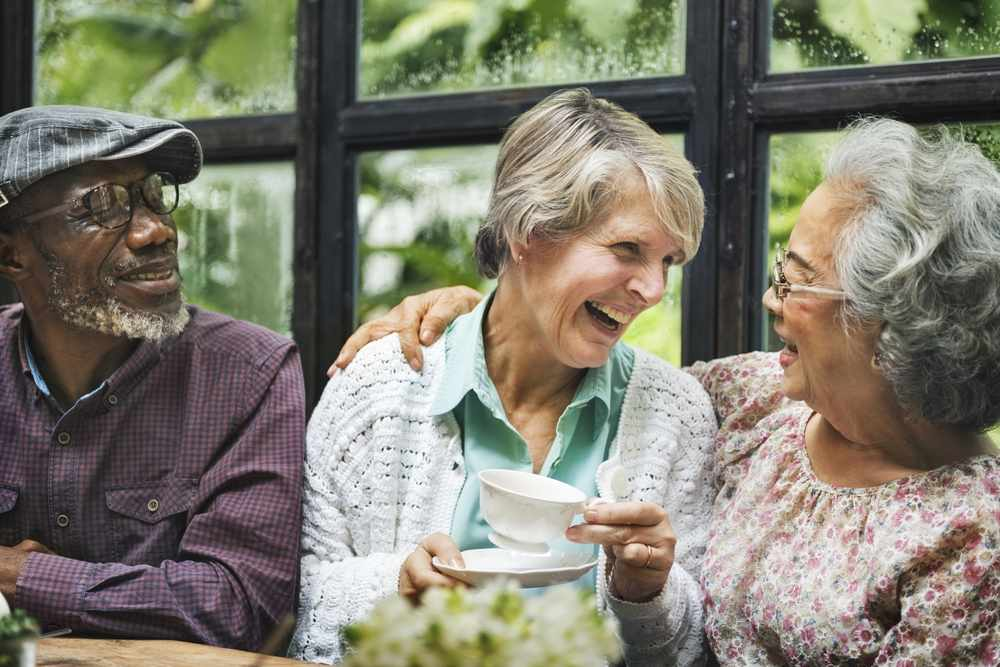 a small group of friends, a older man and two older women, talking and laughing together