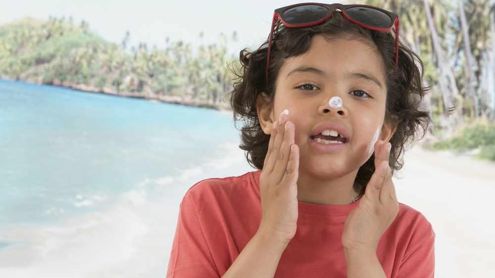 Aumenta el cáncer de piel: un niño muy simpático se aplica protector solar en la cara mientras está en la playa