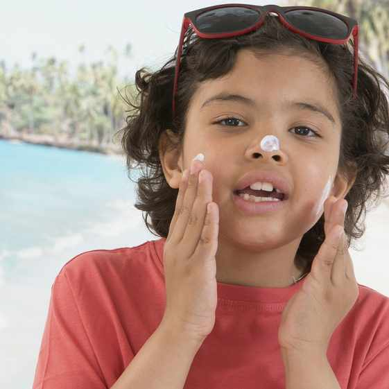 Cute young boy applying sunblock cream on his face on the beach