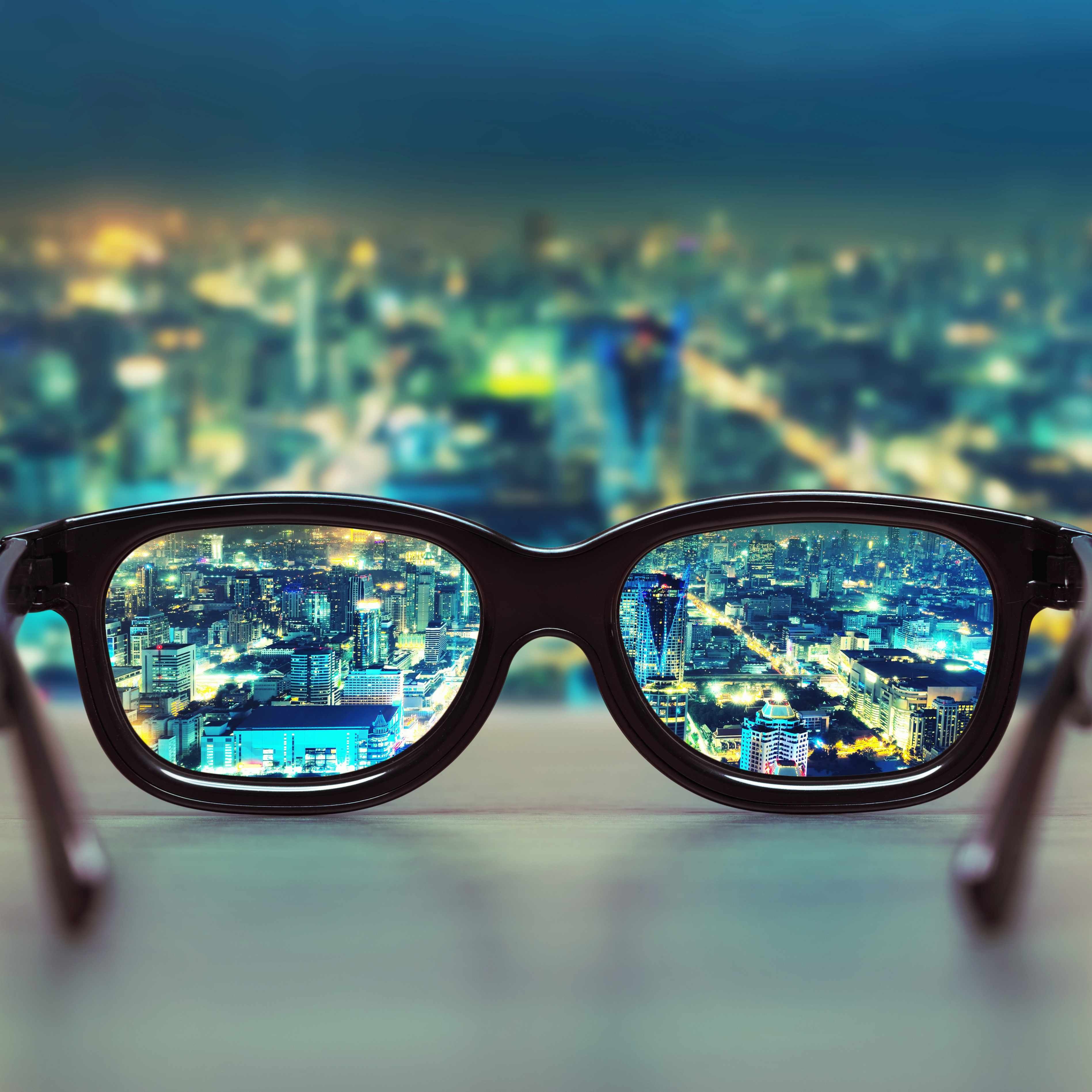a pair of eye glasses on a windwosill with a night scene of a city in the background