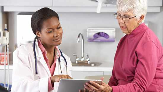 african-american female doctor nurse sharing information with an elderly woman in a hospital room during an appointment