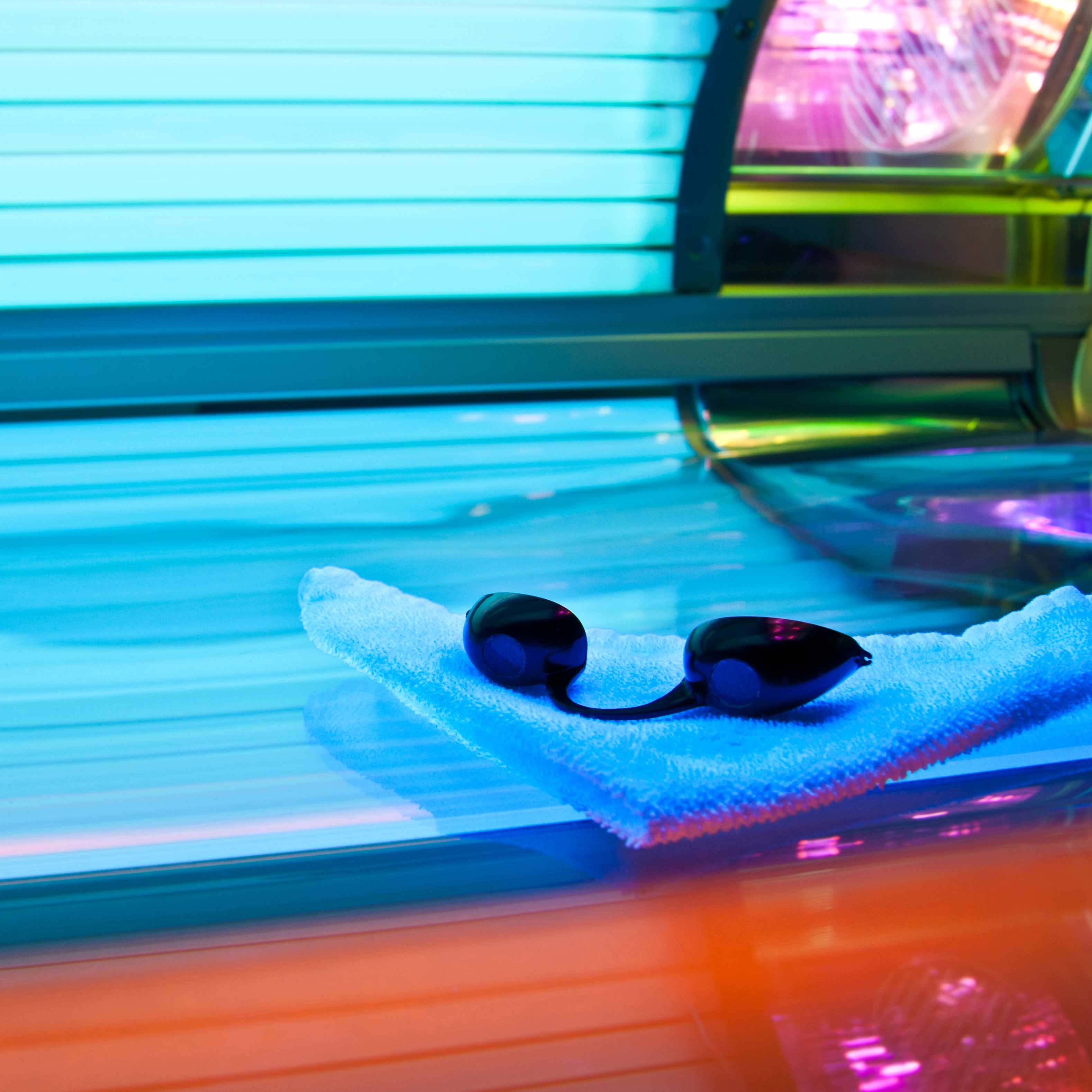 an open tanning bed, with a towel and protective goggles