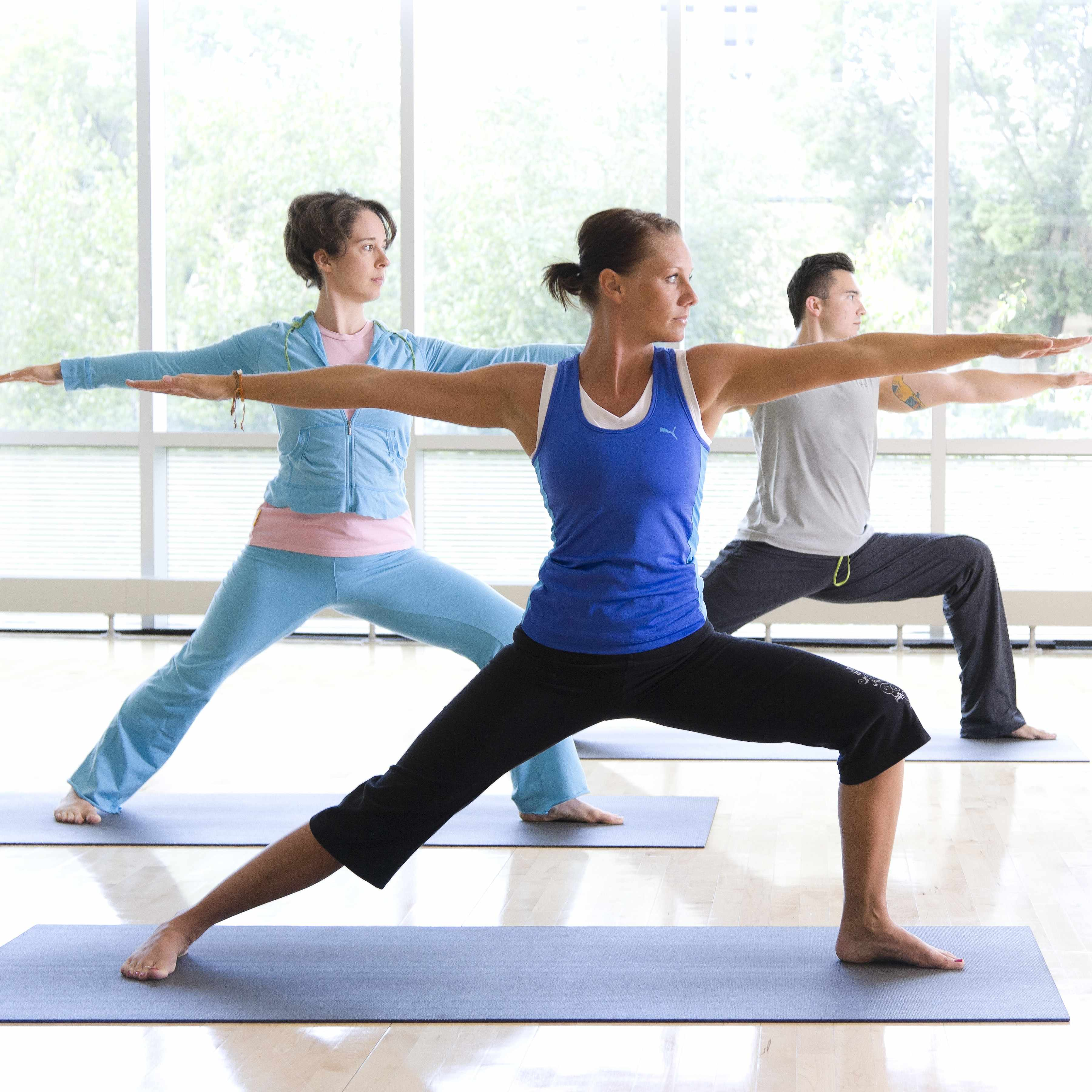 two women and a man doing yoga in front of a wall of windows in a sunny space