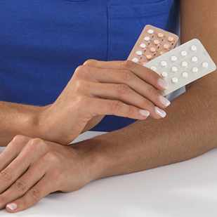woman holding birth control contraceptive pills