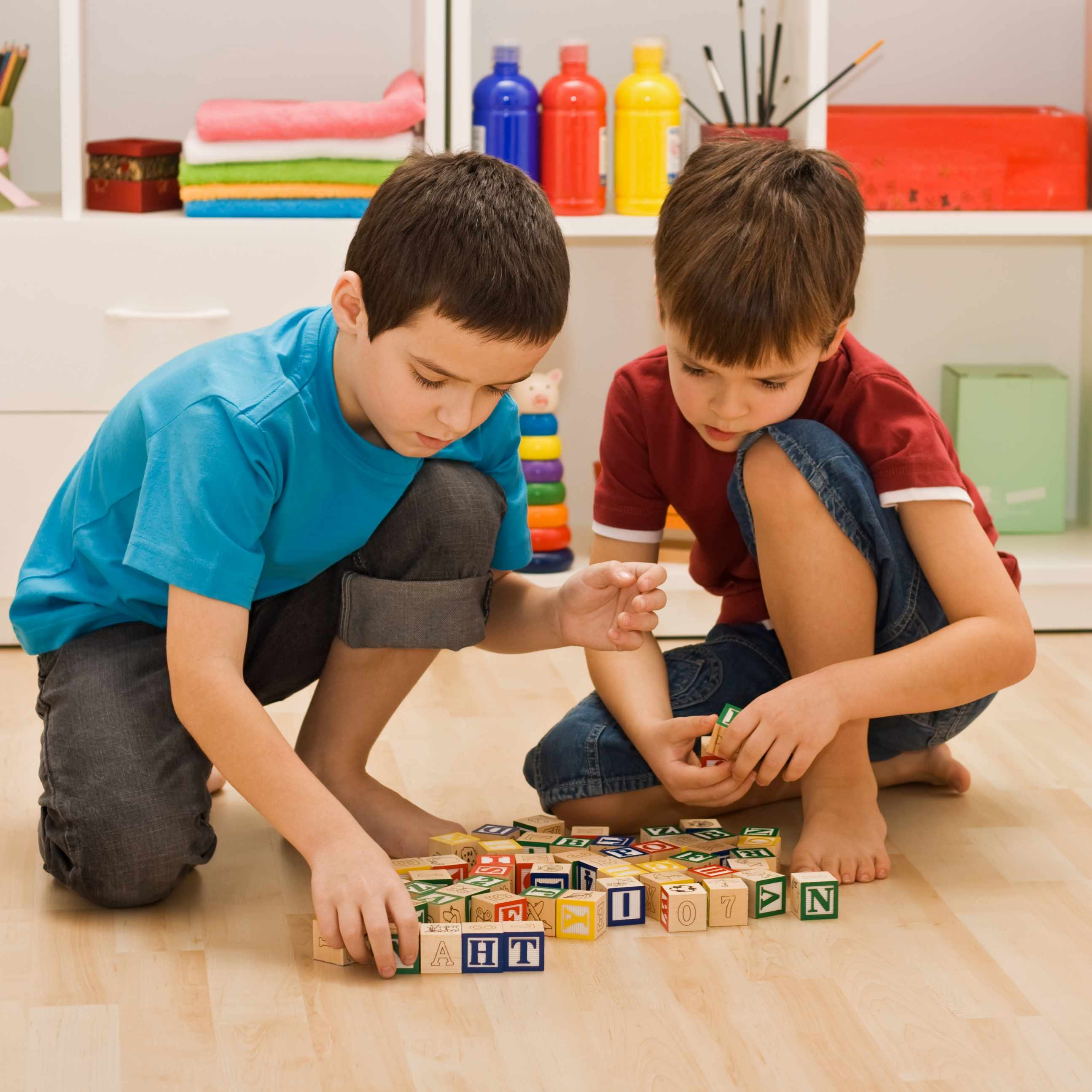 Two little boys playing with blocks on the floor