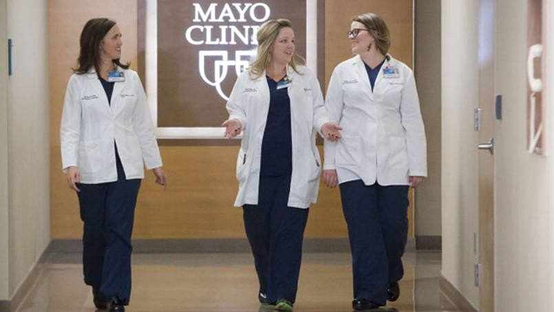 Mayo Clinic staff, three women, walking in the hallway and talking in a walking meeting
