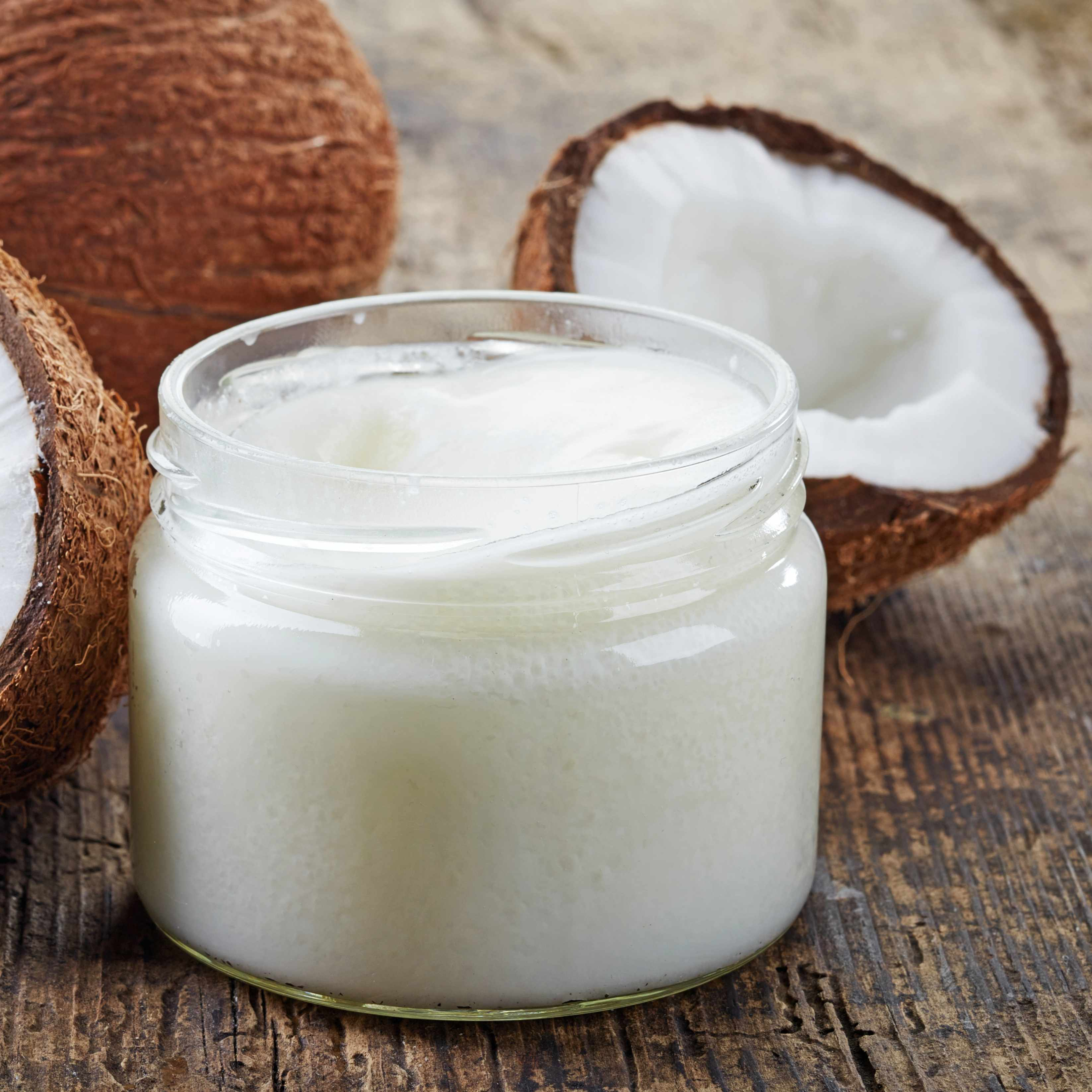 a coconut cut in half, sitting on a wooden table with a jar of coconut oil or butter