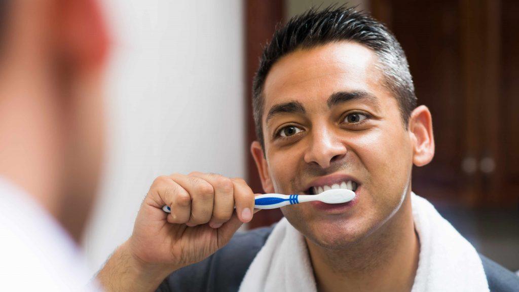 Un hombre mira el espejo del baño mientras se cepilla los dientes
