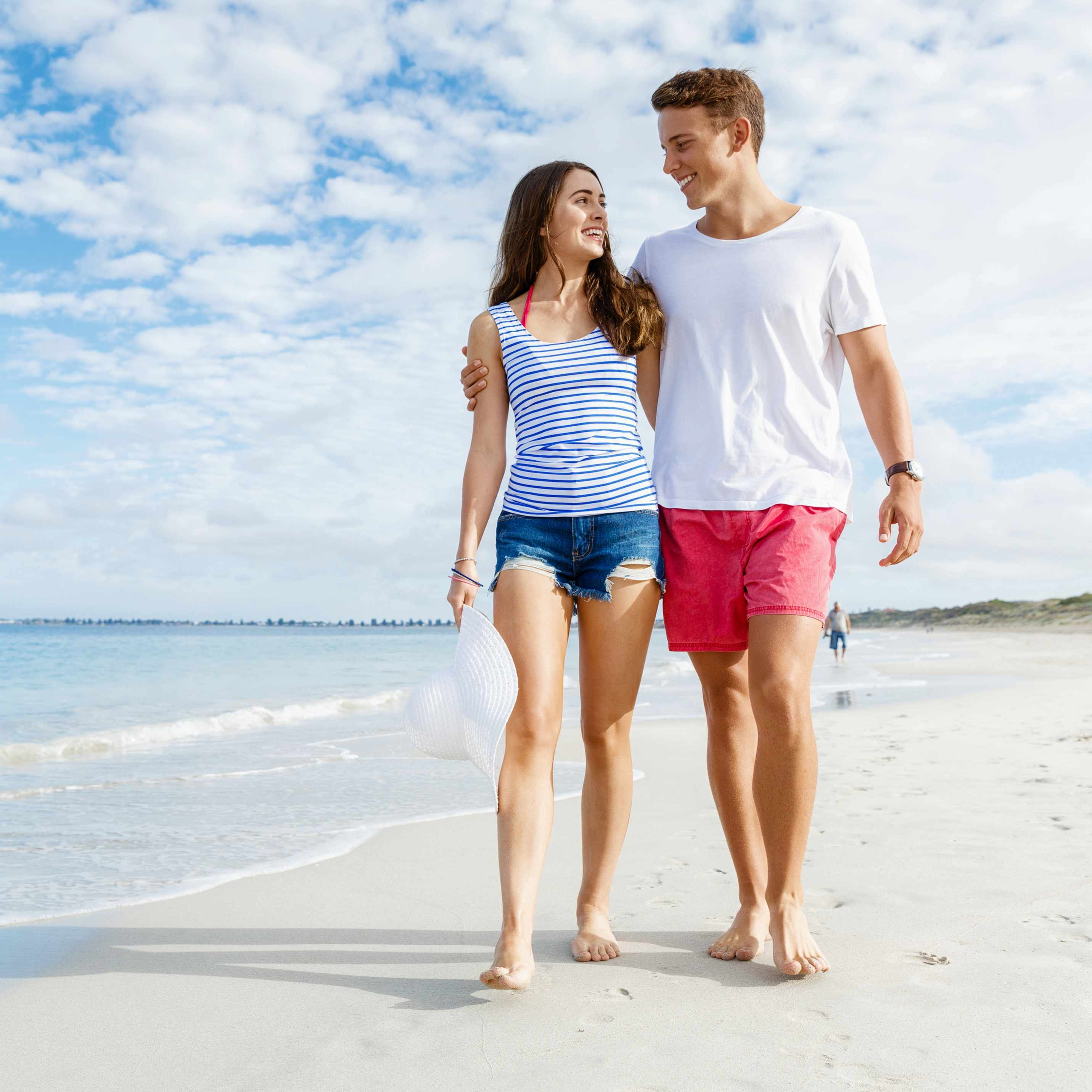 a young couple walking along the beach with blue sky in the background