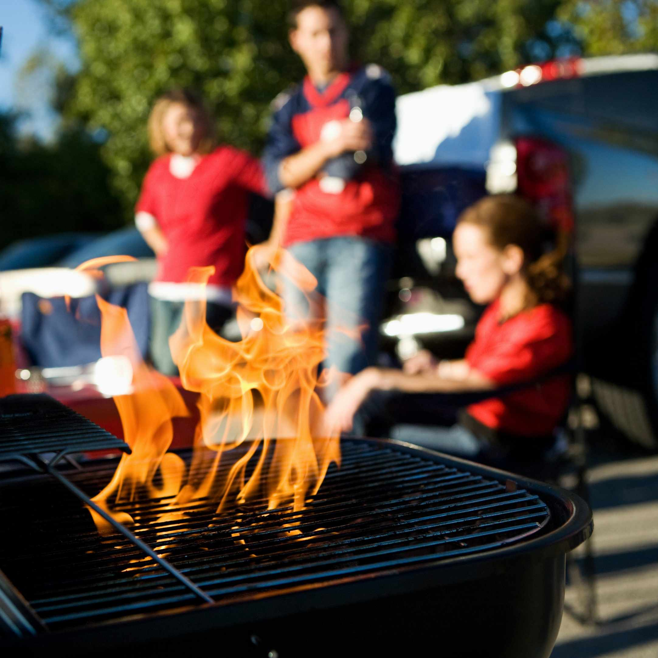 a group of friends gathered outside to cook with flames leaping up from the grill