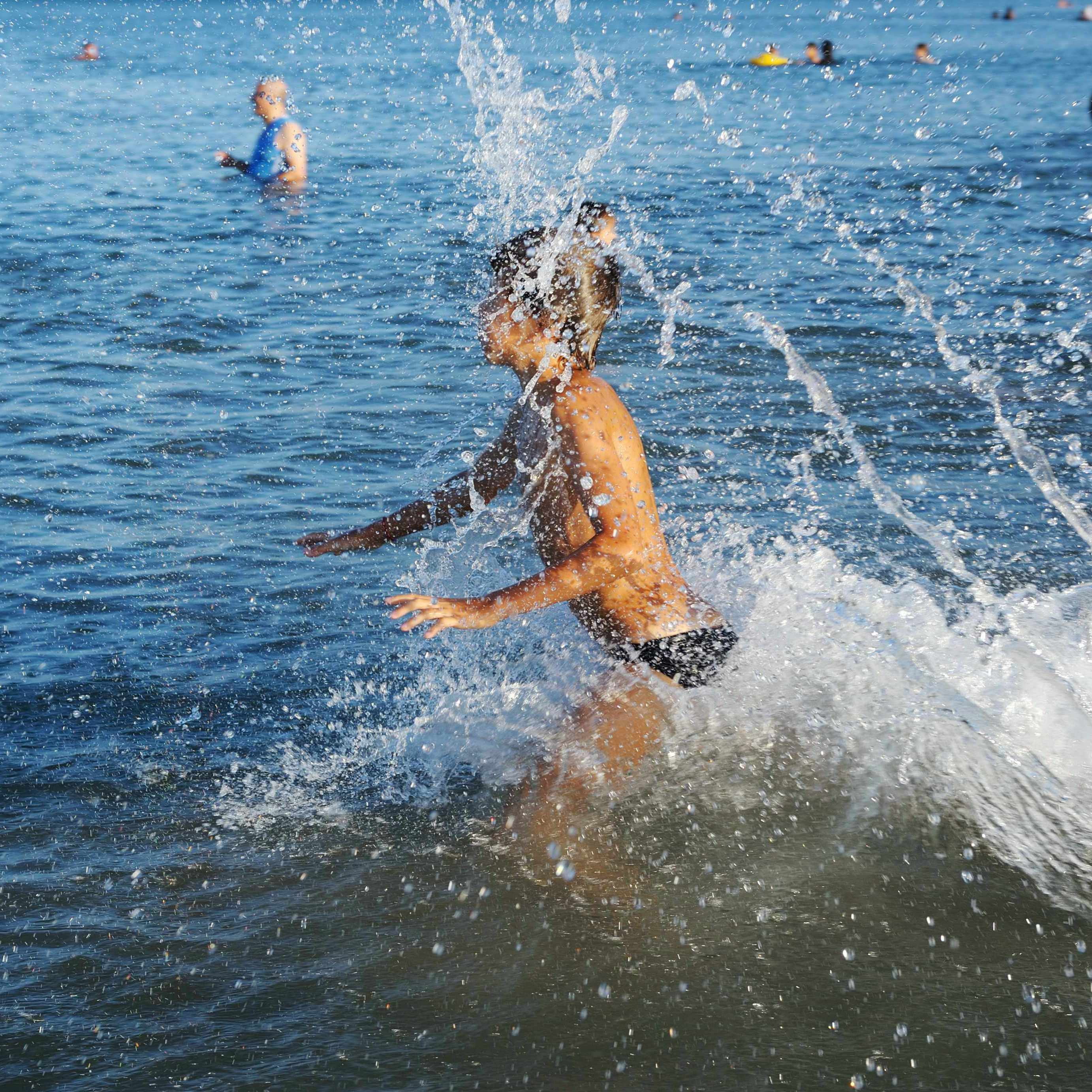 people in lake water swimming and a young child splashing through the water