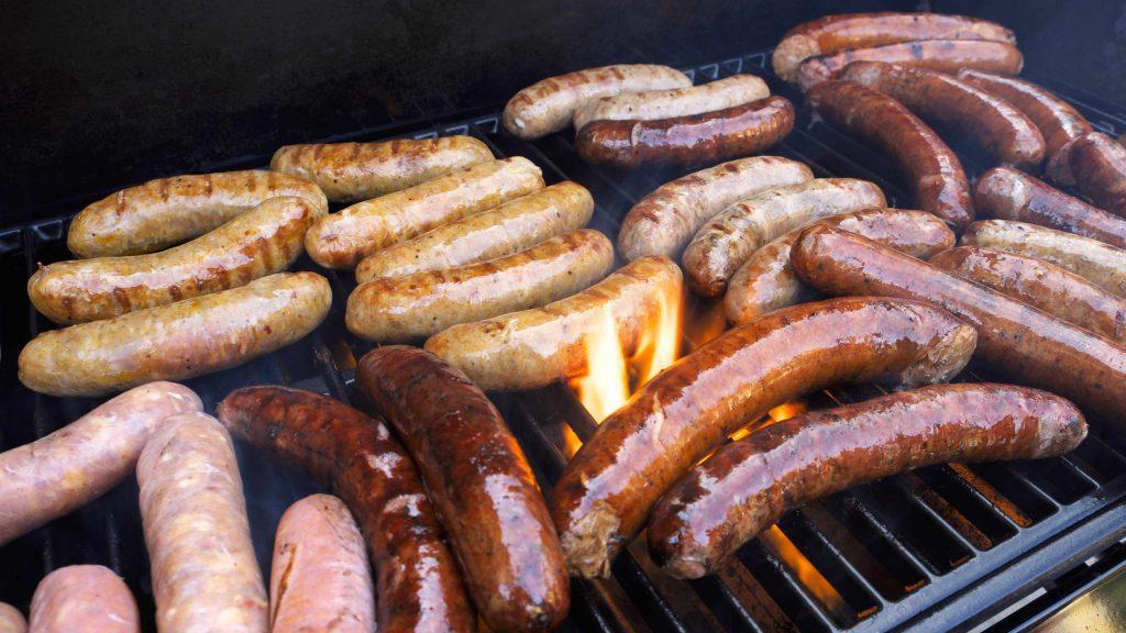 Carne roja procesada, como perros calientes y salchichas, sobre una parrilla.