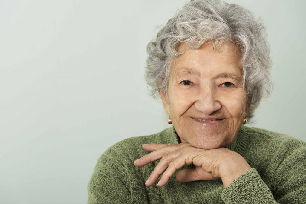 a close-up of a happy, smiling older woman, with her chin resting on her hand