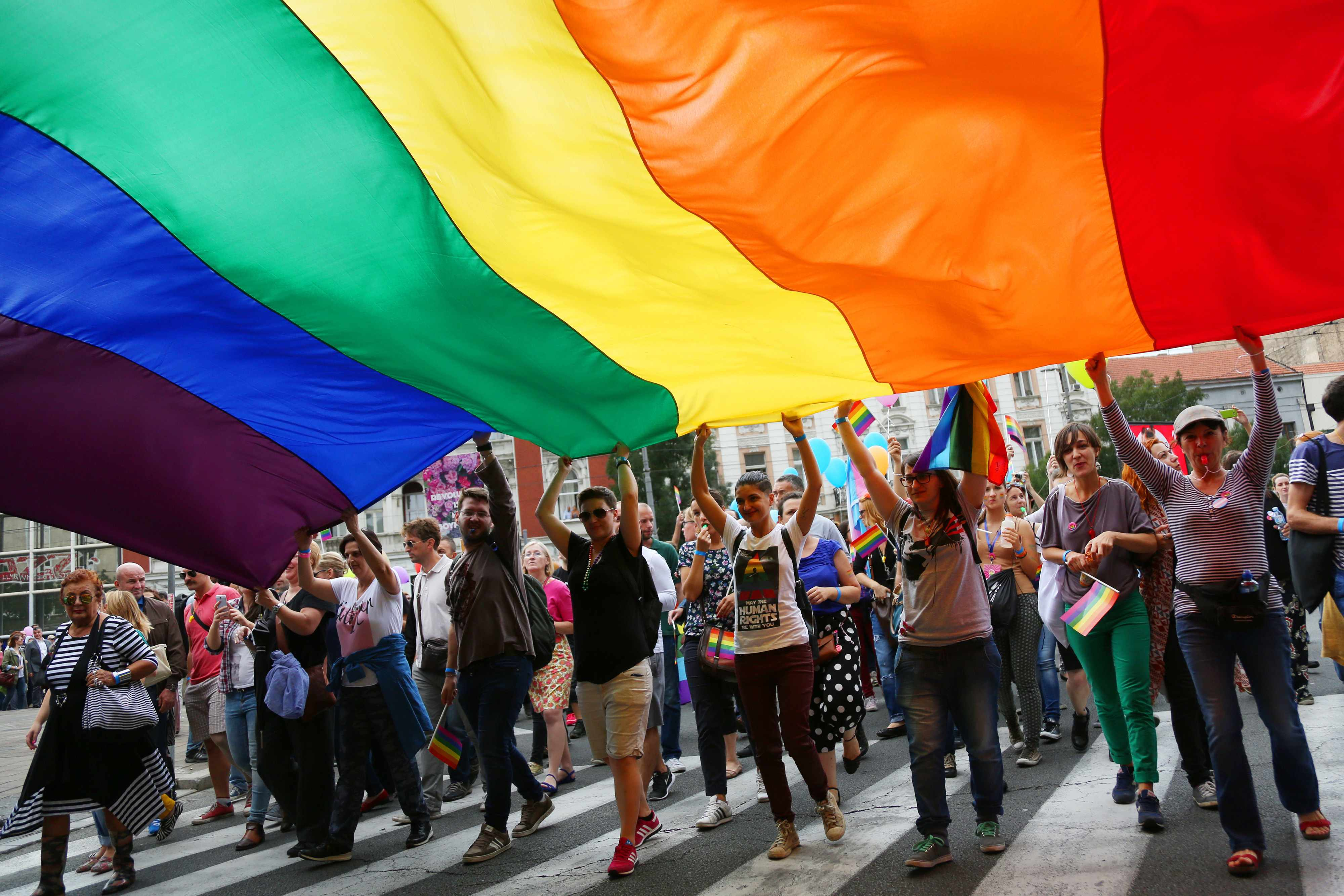 a group of smiling people in a Gay Pride parade, holding a large rainbow banner
