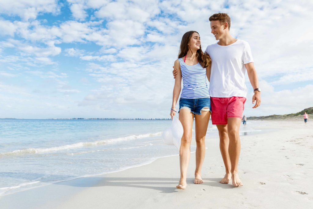 a smiling young couple walking along the beach with their arms around one another, with blue sky in the background