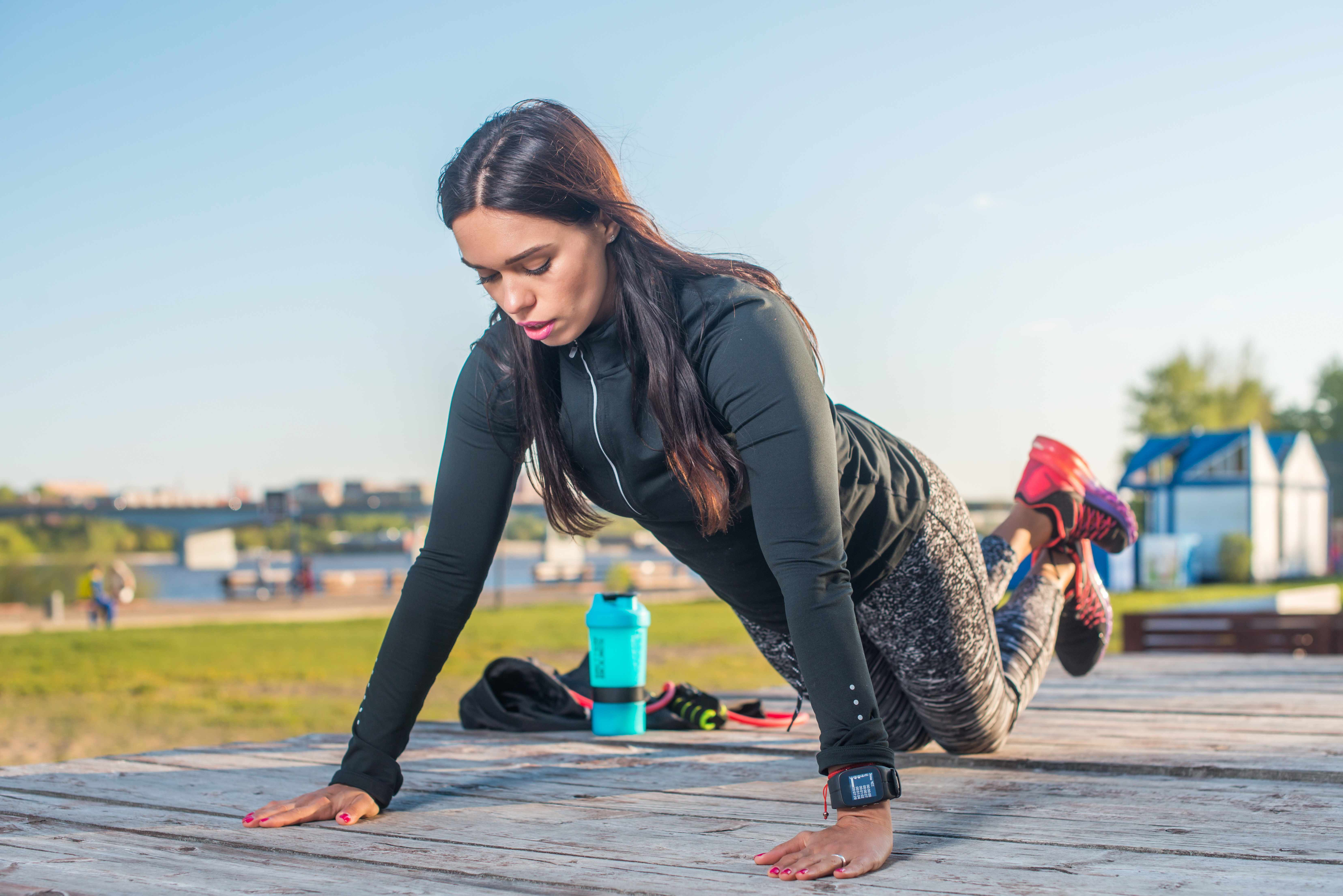a young woman doing knee pushups on an exercise board outside