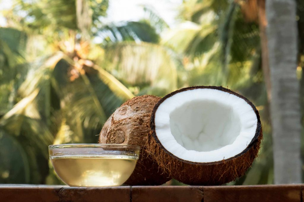 a coconut cut in half, placed on a bench with a glass bowl of coconut oil and palm trees in the background