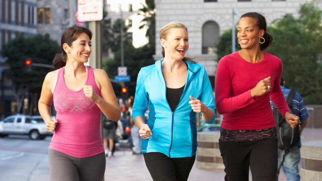 three smiling young women walking vigorously along a city sidewalk