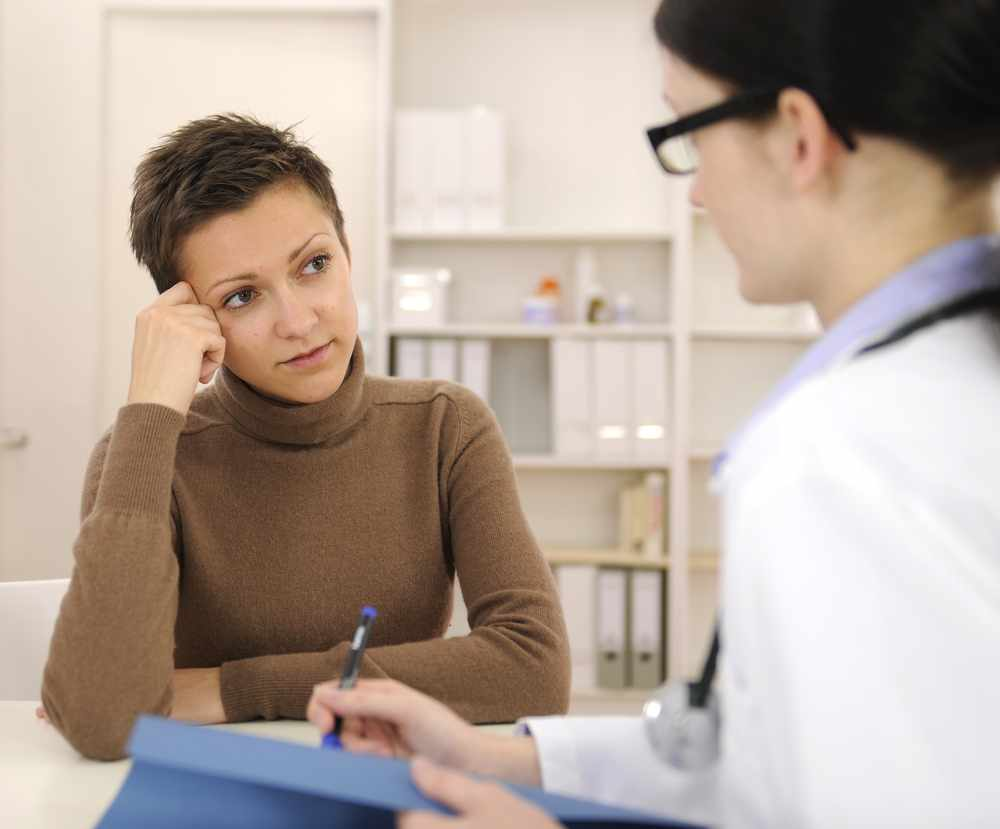 worried female patient at female health care provider's office during consultation