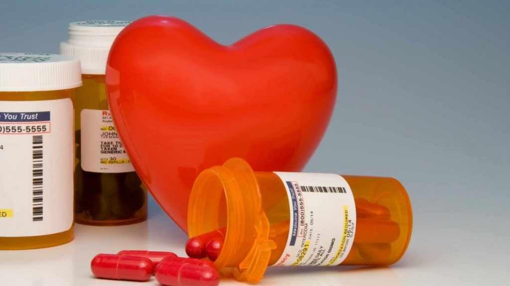 Un corazón de plástico junto a unos frascos de medicamento