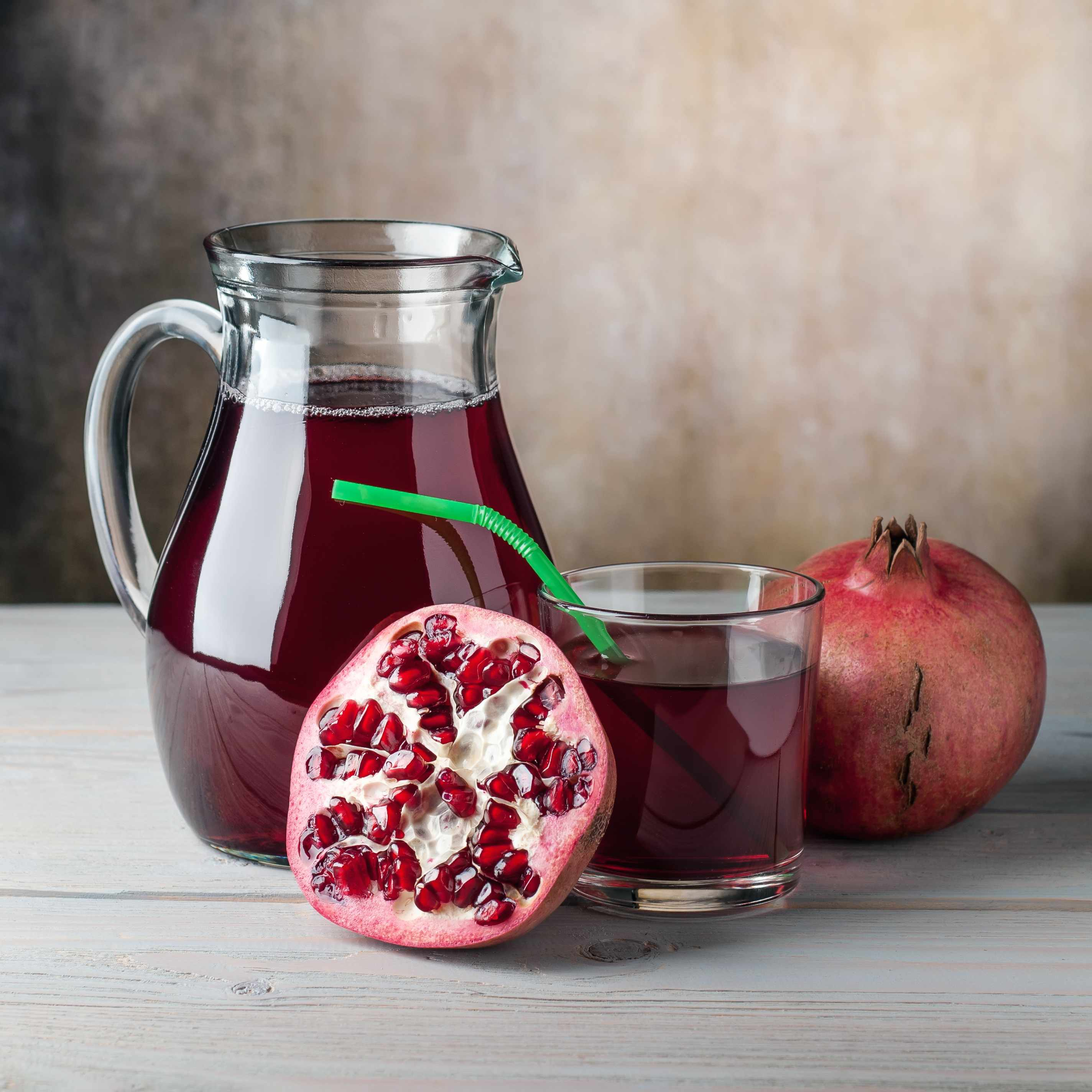 a whole pomegranate, one cut in half, and pomegranate juice in a pitcher and a glass