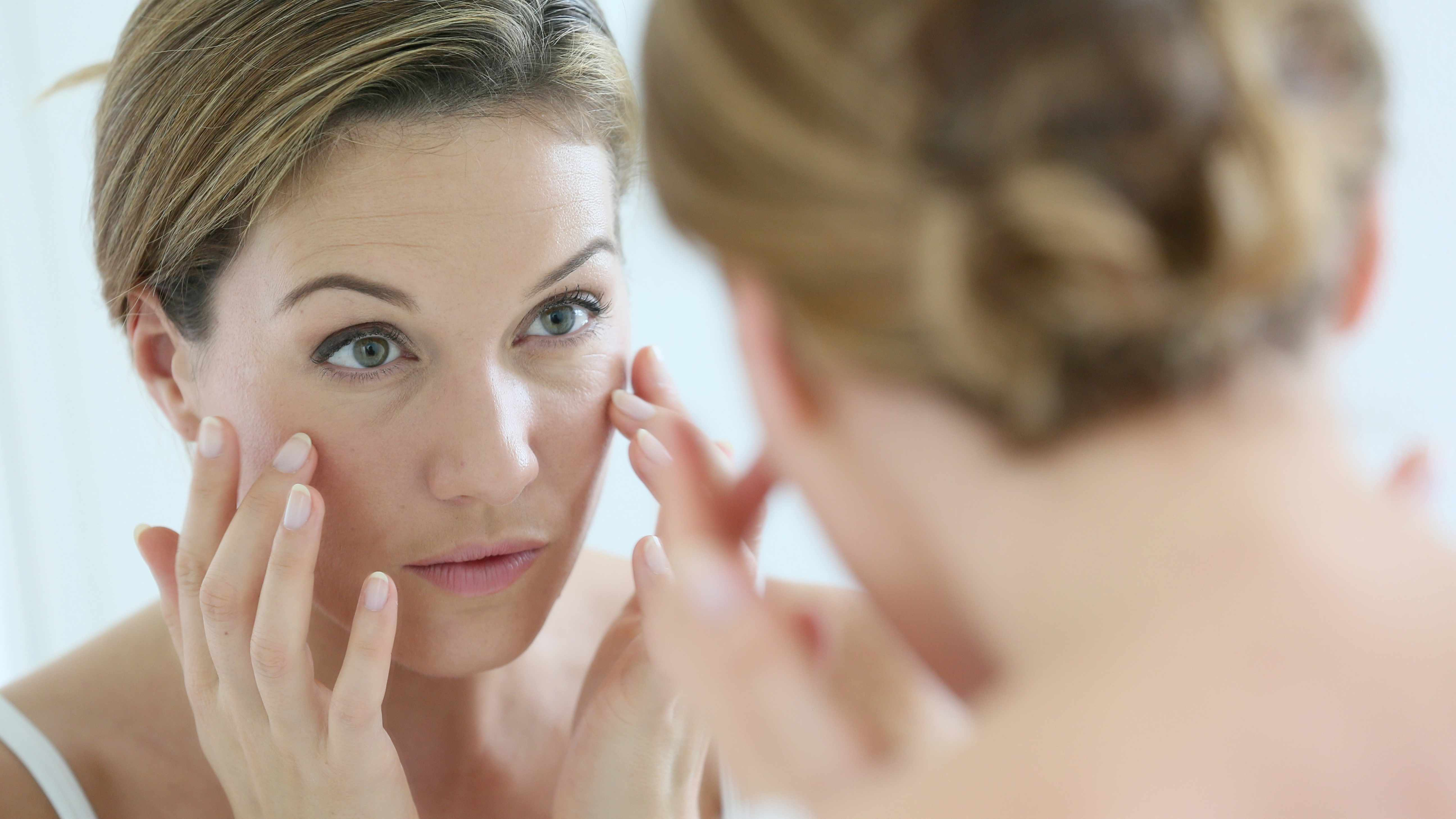a woman looking in a mirror touching her face and looking for wrinkles