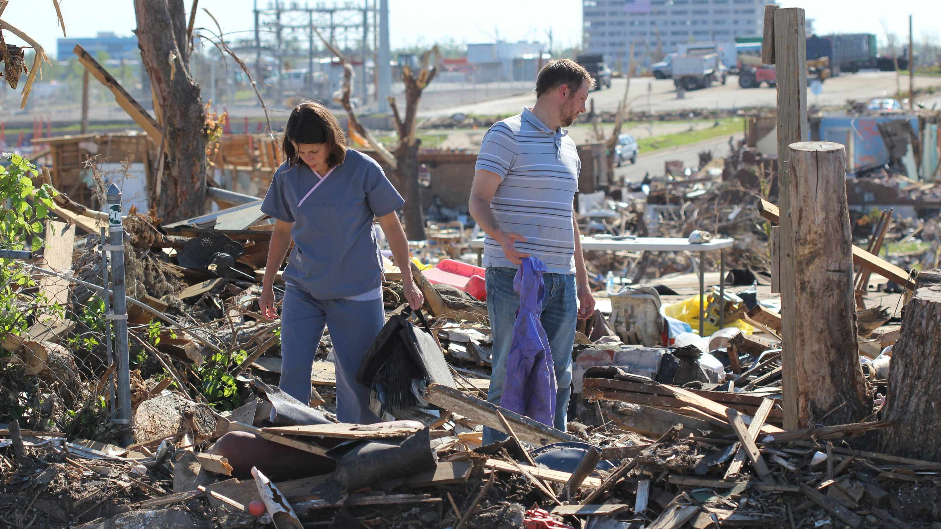 a young couple walking through debris from their home after a storm