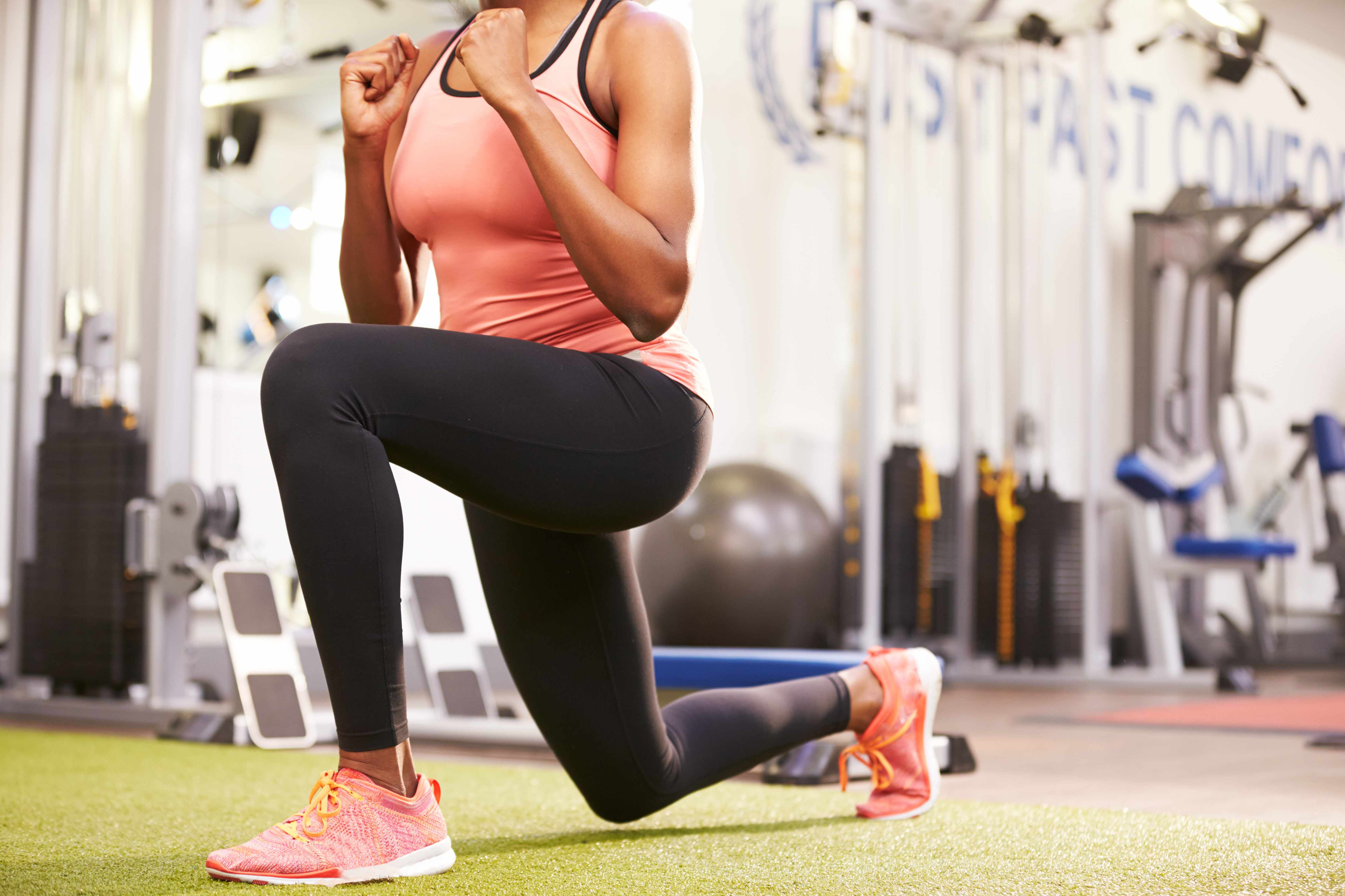 a woman doing walking lunges in a exercise gym