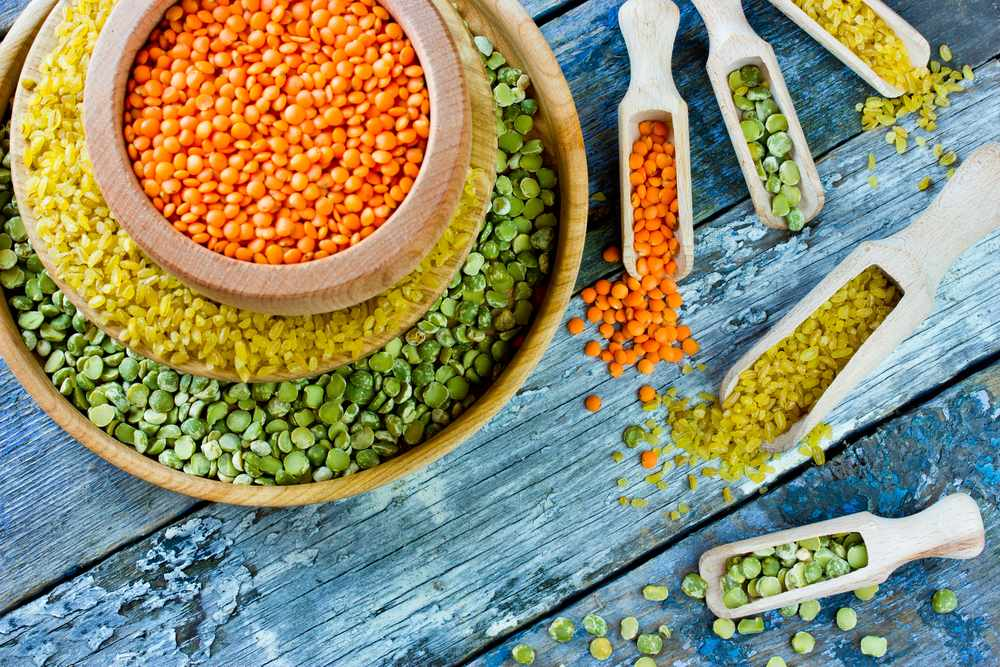 a display of red lentils, yellow bulgur and green split peas, in stacked wooden bowls and small scoops, all on a background of rough wood