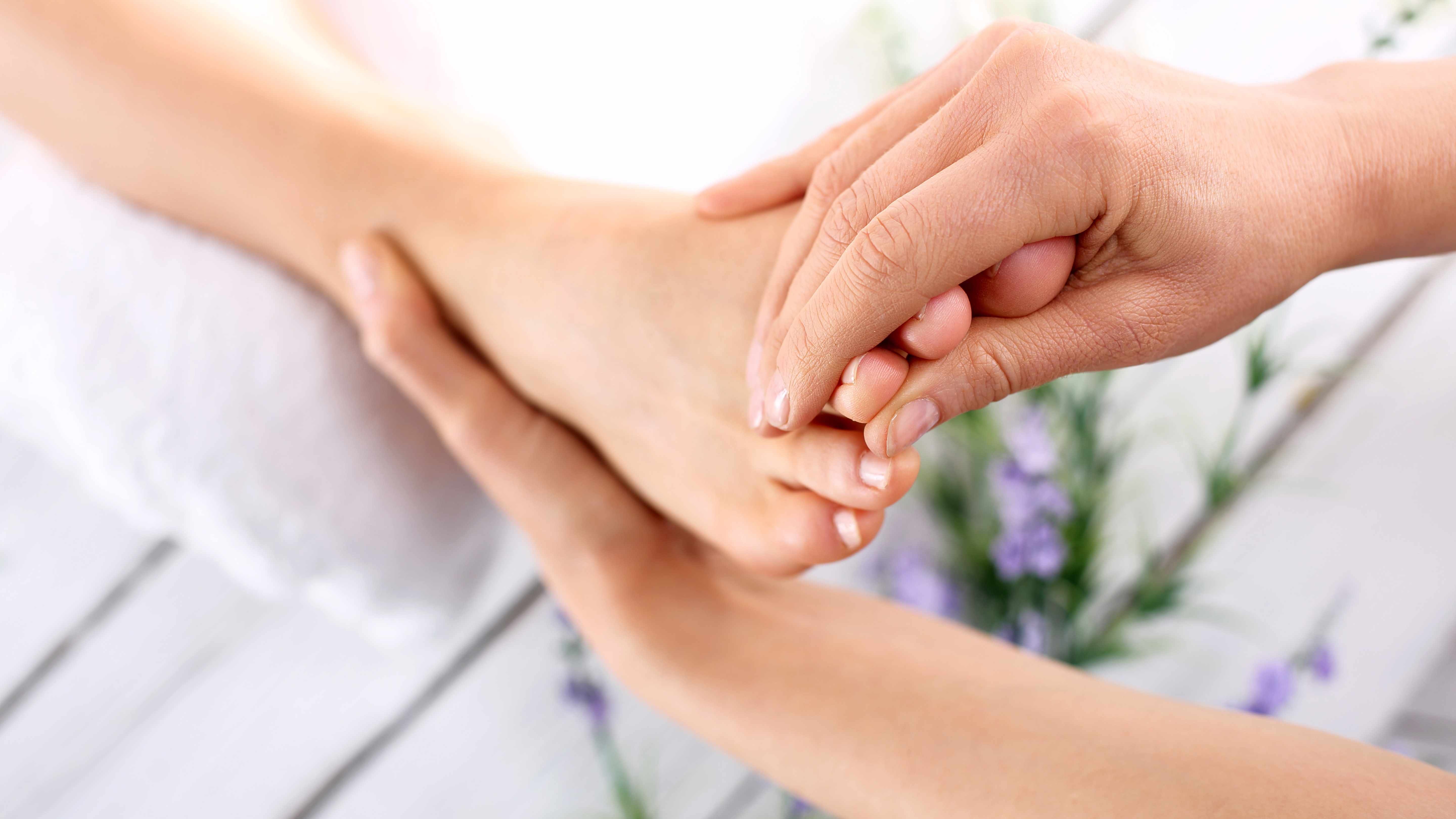 two hands grasping another person's foot at the heel and toes, performing massage or reflexology