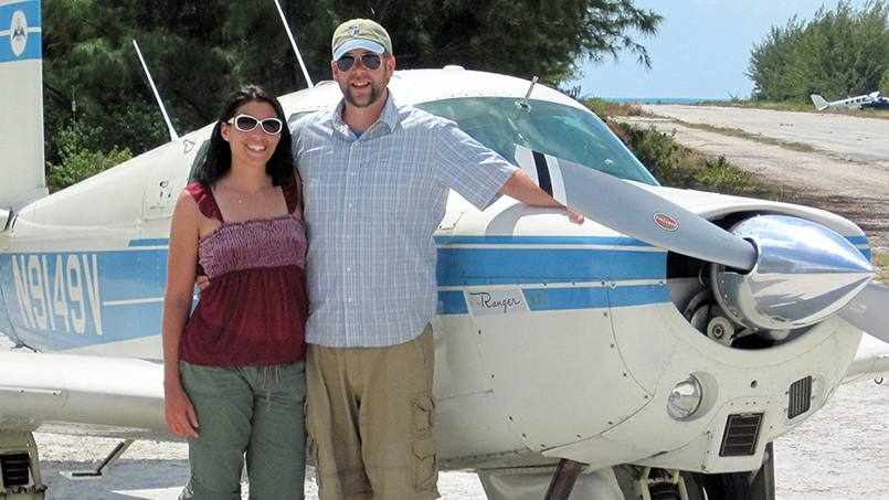 patient Dan Bass standing with his wife and an airplane is behind them
