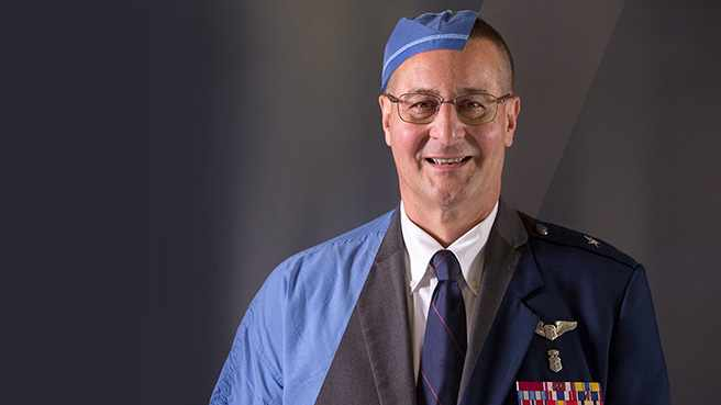 Dr. Michael Yaszemski in medical scrubs and military uniform