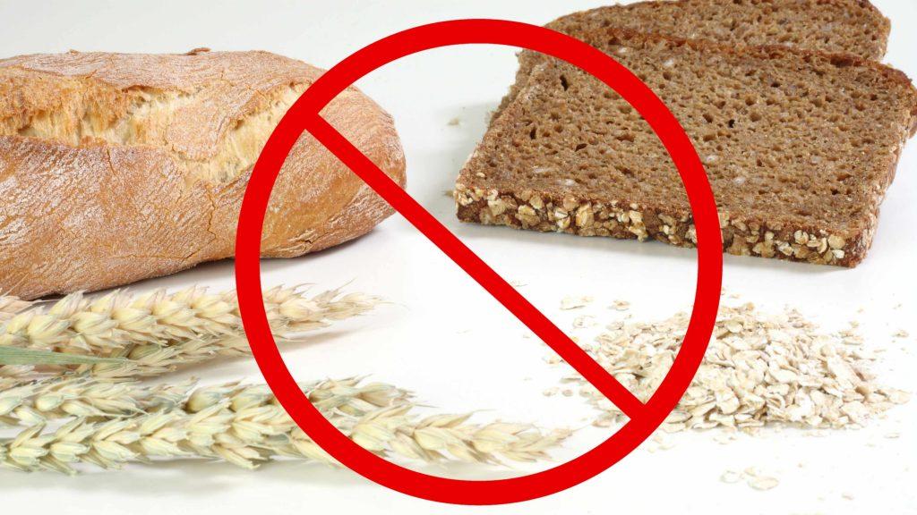 """El símbolo de """"no"""" sobrepuesto a un grupo de granos de trigo, cereales y pan"""