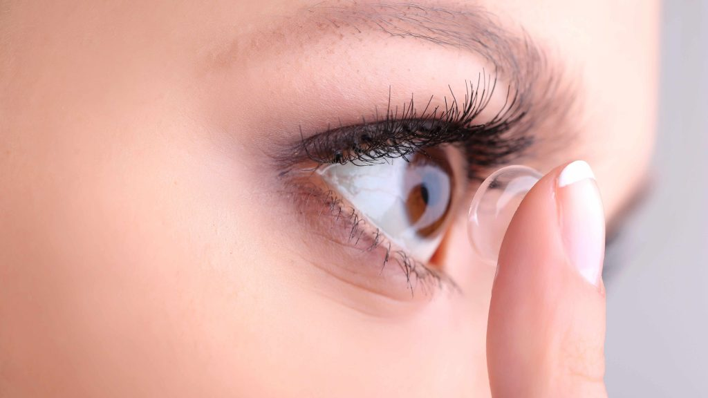 a close-up of a young woman inserting a contact lens into her eye