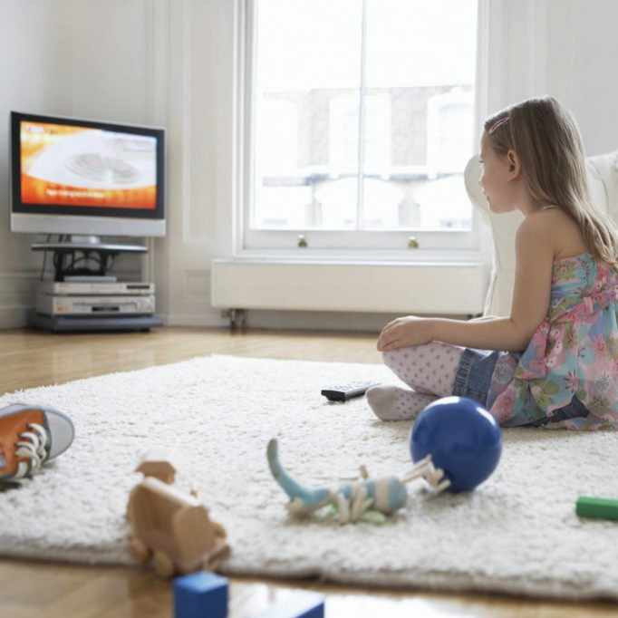 a little girl staring at a television screen, watching TV