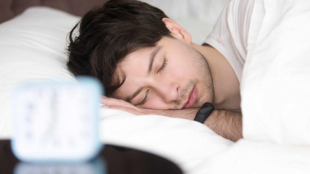 Un hombre dormido en la cama con un medidor de actividad física en la muñeca