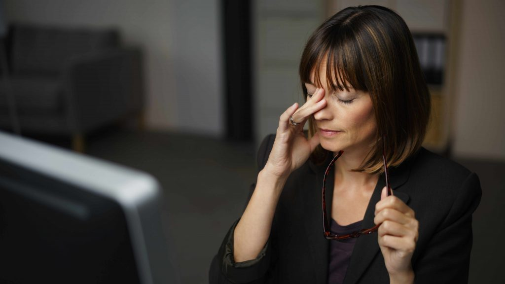 Una joven sentada en la oficina frente al computador luce cansada y se toca la cara como si tuviera dolor de cabeza