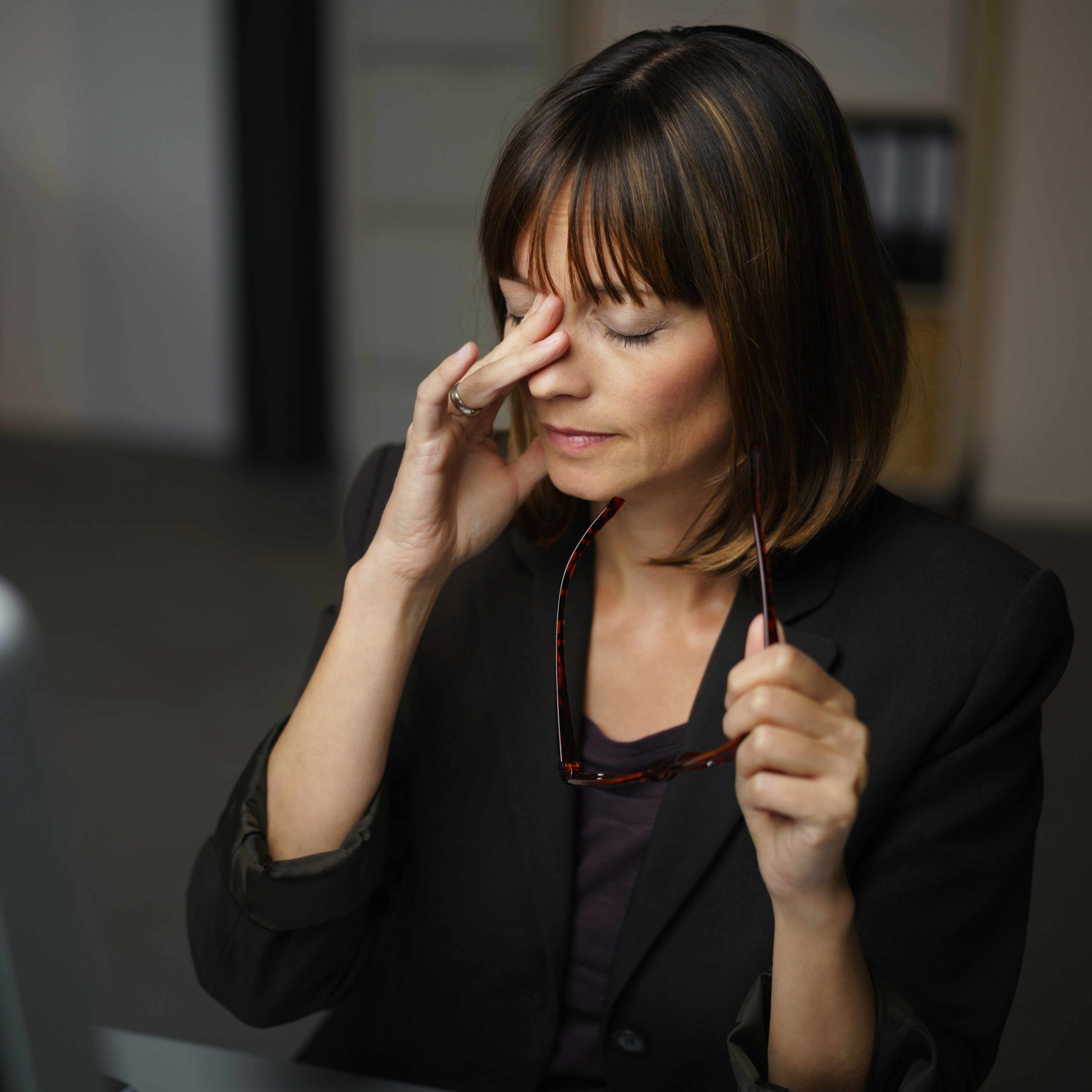 a young woman sitting at a computer in an office looking tired and touching her face like she has a headache