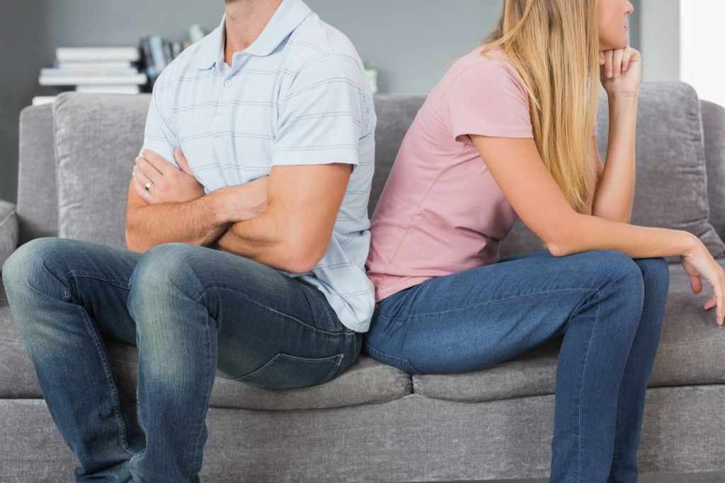 a man and woman sitting back to back after argument, hurting each other
