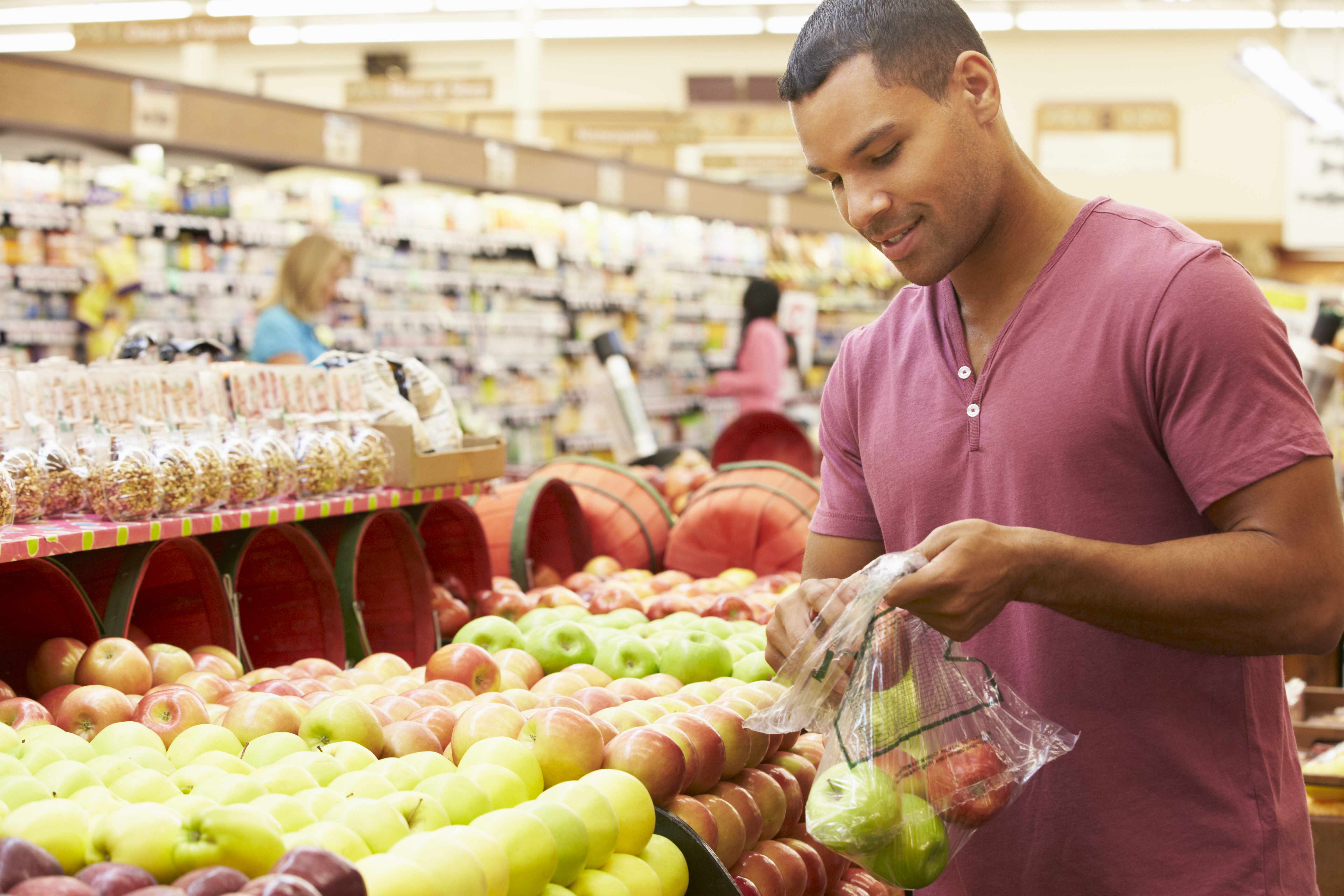 a young African-American man grocery shopping in a store for healthy food, picking fruits for his bag
