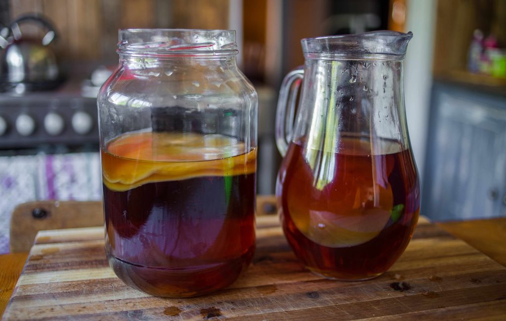 kombucha tea in a jar and a pitcher, on a woodern surface, in a home kitchen